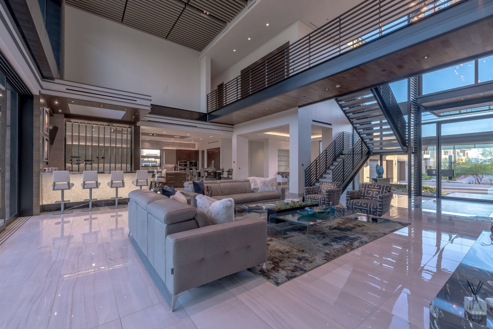 The interior of a modern home with a metal artisan staircase by JD Stairs