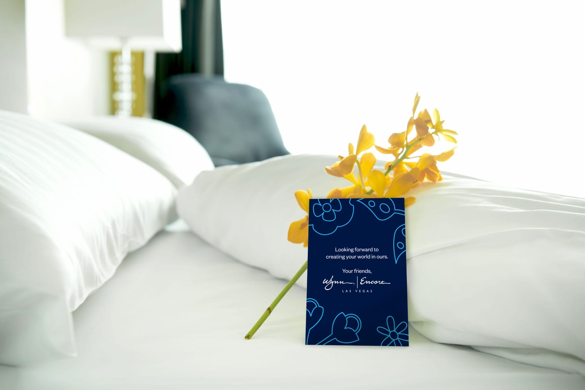An Wynn Las Vegas amenity card placed on a bed with a flower