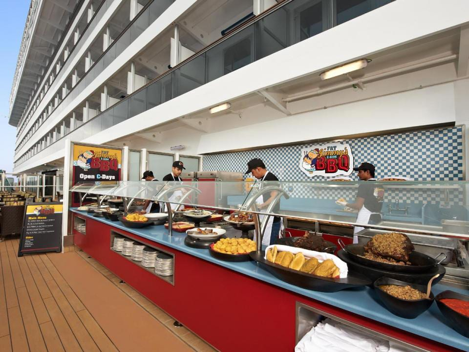 On the deck of the Carnival Cruise Line with Fat Jimmy's C-Side BBQ. A buffet of food.