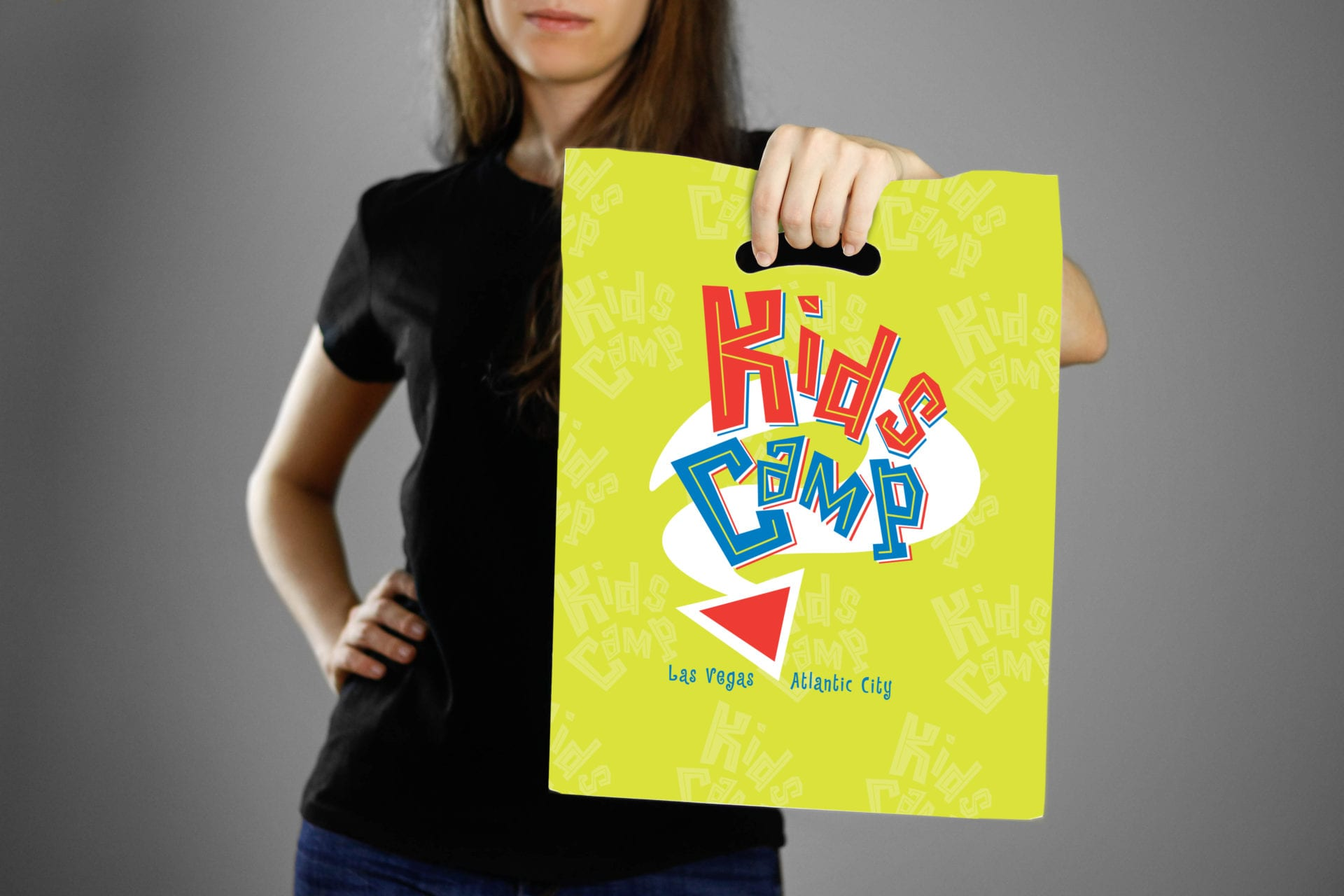 A woman holding a Marshall Retail Group Kids Camp branded bag