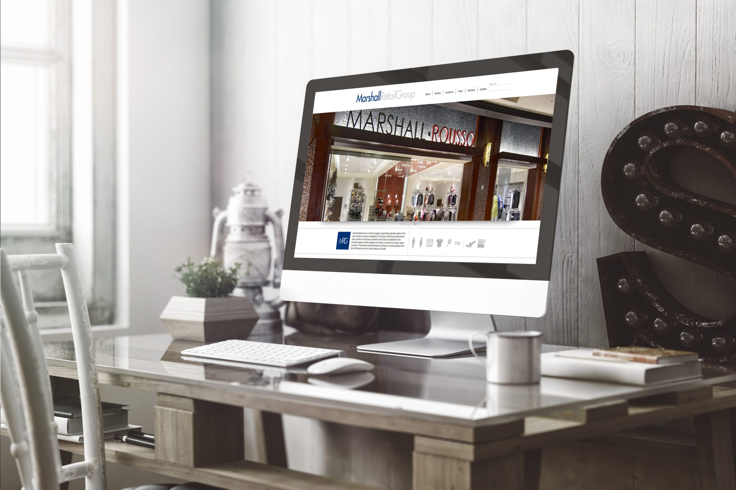 A desktop computer displaying the Marshall Retail Group website designed by Canyon Creative.