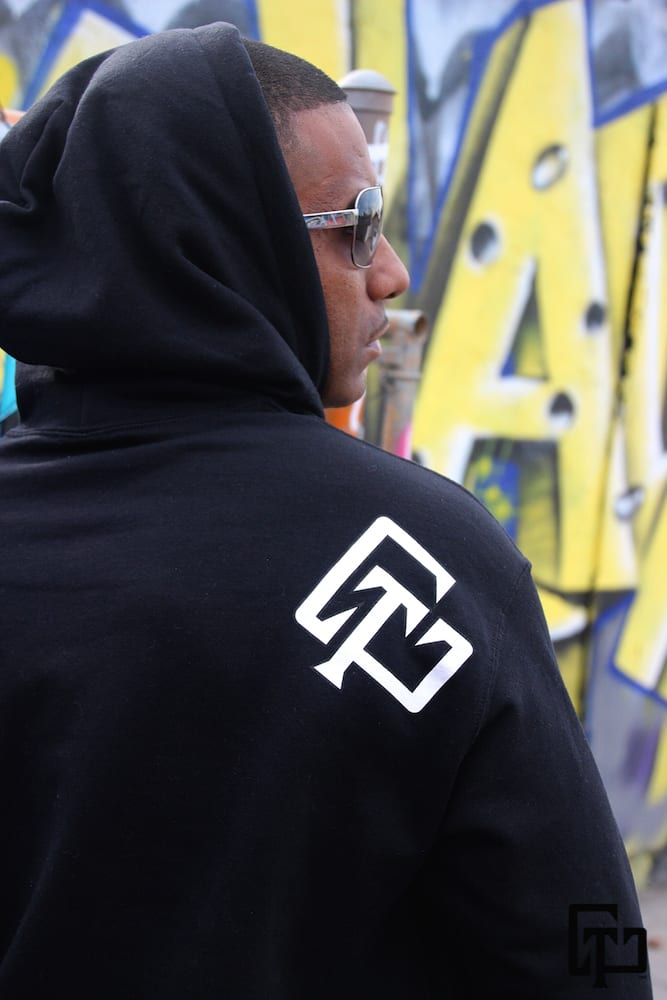 A man wearing a black U Chase This branded hoodie