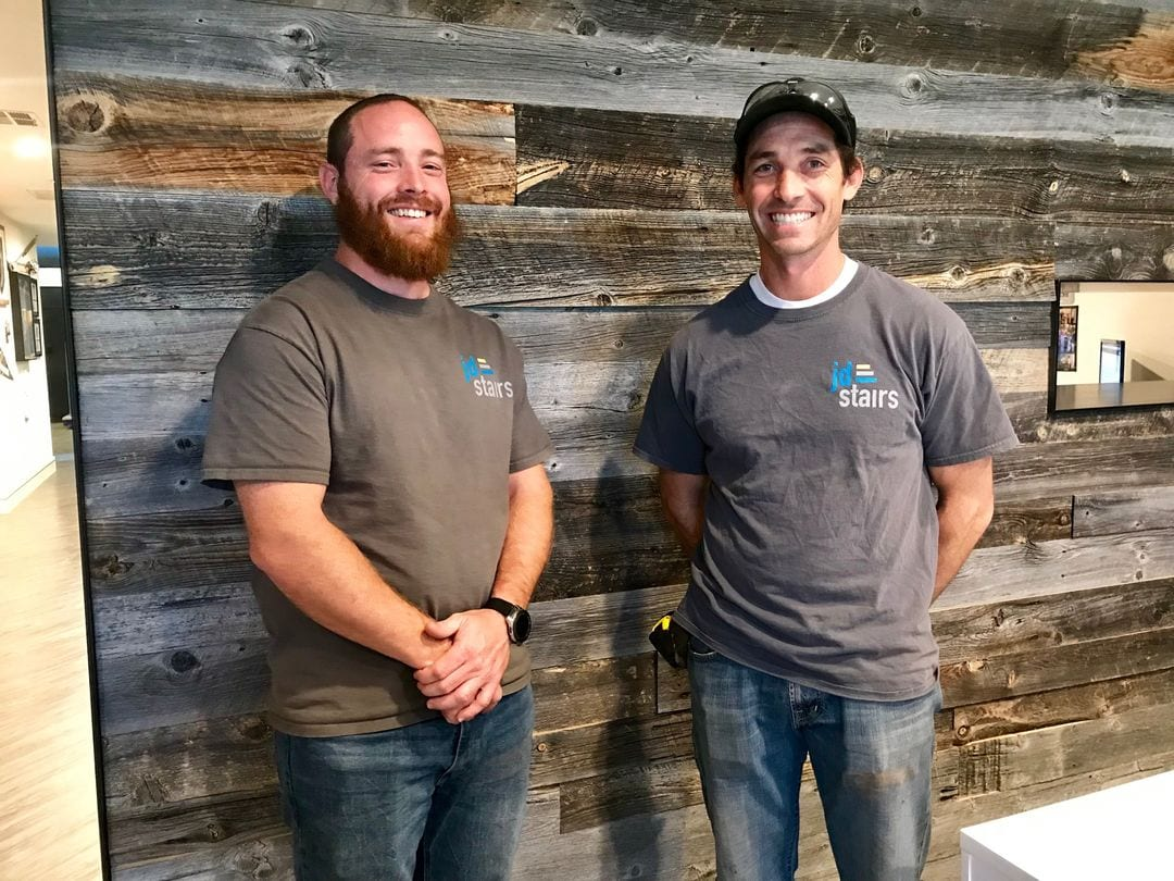Donald and Jonathan Webster of JD Stairs in front of their plank wood wall created by reclaimed family barn wood